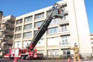 △消防職員が屋上の要救助者2名(模擬患者2名)をはしご車で救助。